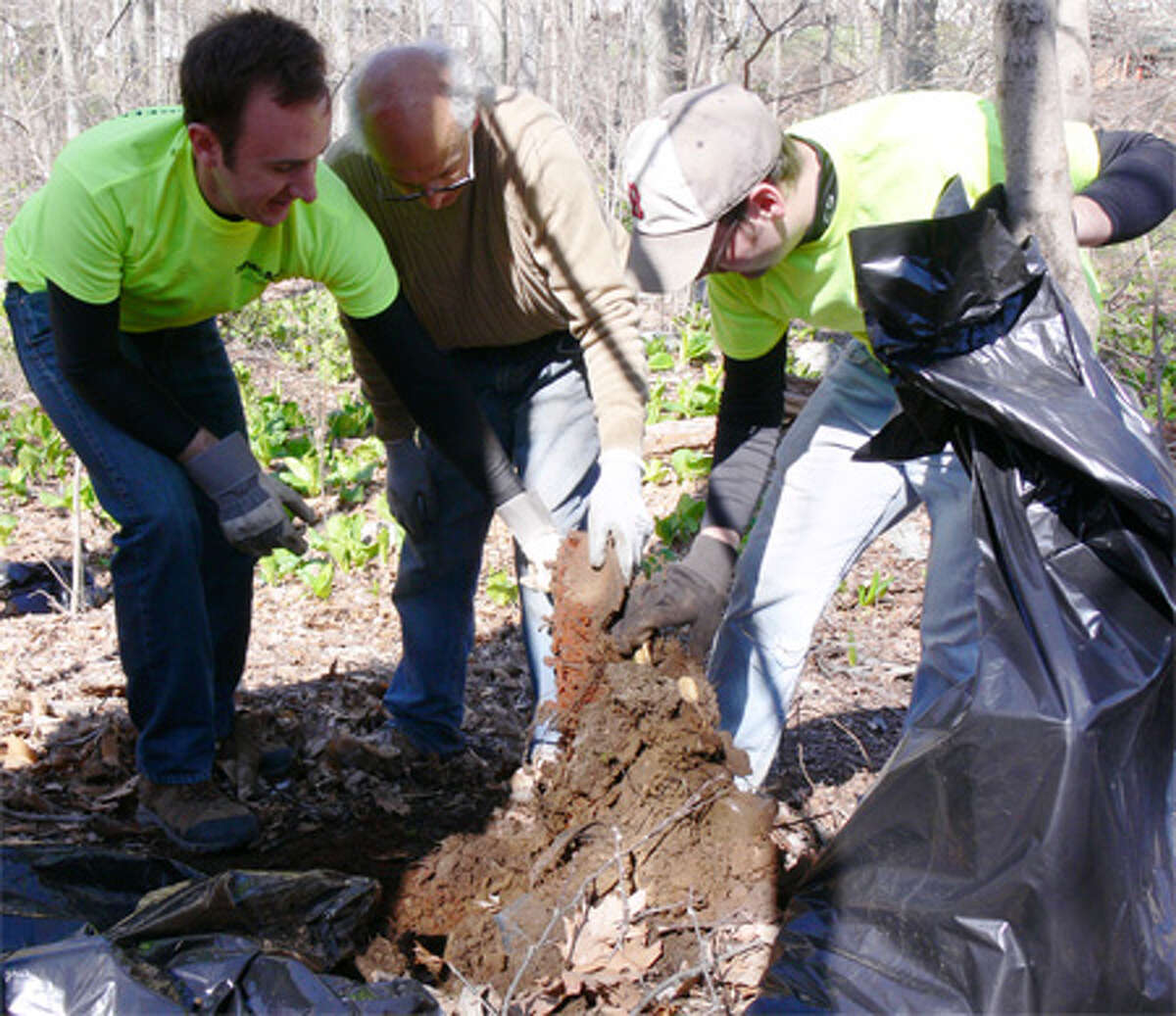 From left, Shelton residents Chris Dubuque, John Penelli and Tim Schwartz pull an old, rusted metallic car part out of the ground for proper disposal.
