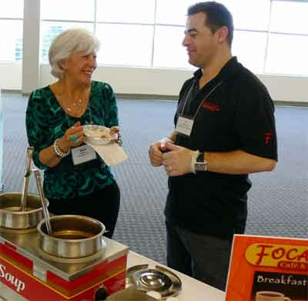 Debi Molfese of BeautyCounter, a home-based business in Seymour, tries the soup from Focaccia's Cafe in Shelton while chatting with Focaccia's co-owner Ben Mujollari during the business expo. Focaccia's is in the Center at Split Rock shopping center on Bridgeport Avenue.