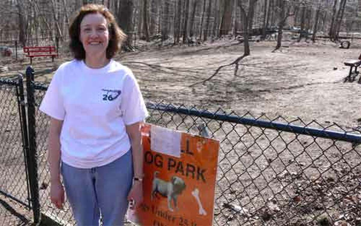 Carol Pendergast takes a break from her spring cleaning duties at the Shelton Dog Park.