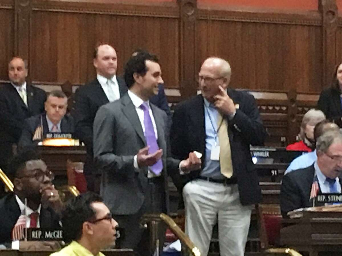 Rep. Michael D'Agostino, D-Hamden, (left) spoke to Rep. Phil Young, D-Stratford, (right) in the final minutes of the 2019 General Assembly session.