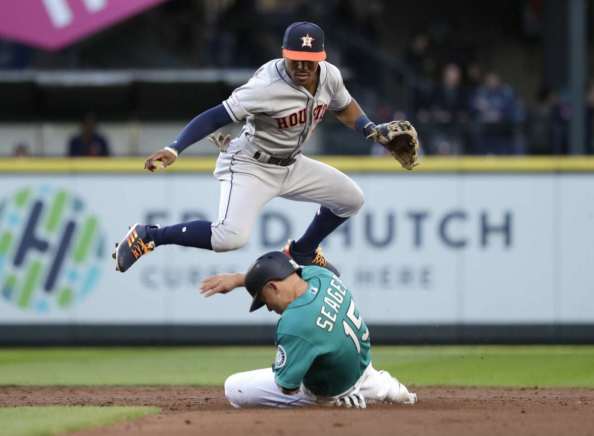 Houston Astros second baseman Tony Kemp leaps out of the way as Seattle Mariners' Kyle Seager slides into second in the second inning of a baseball game Wednesday, June 5, 2019, in Seattle. Seager and Domingo Santana, at first base, were both out on the double play. (AP Photo/Elaine Thompson)