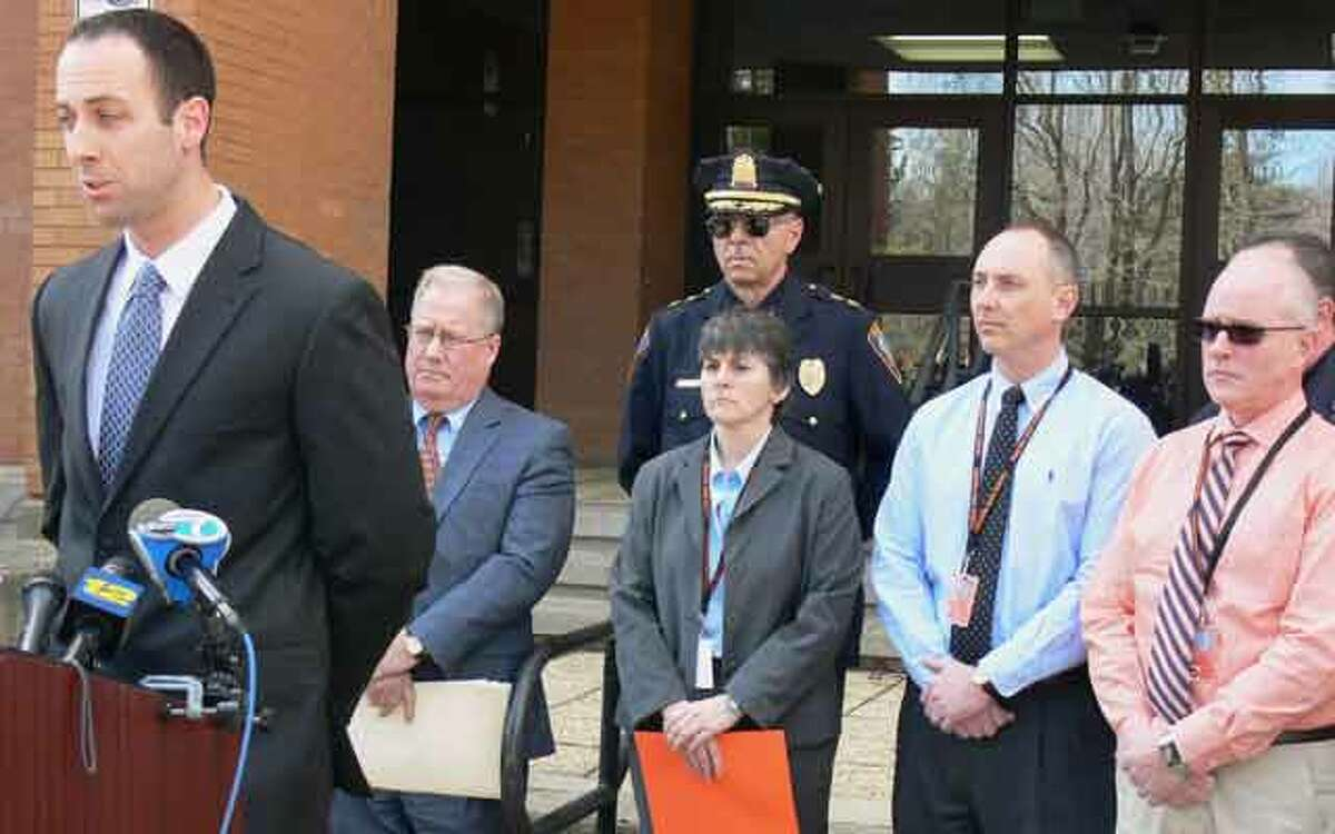 Shelton Police Lt. Robert Kozlowsky, left, answers questions from the media at Shelton High School while surrounded by school and police officials and a Ndoj family spokesman.