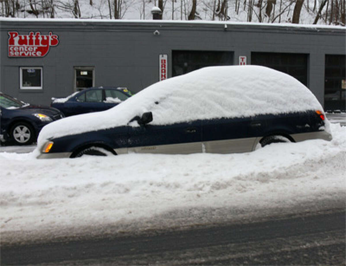 A snow-covered vehicle on the side of the road in downtown Shelton.