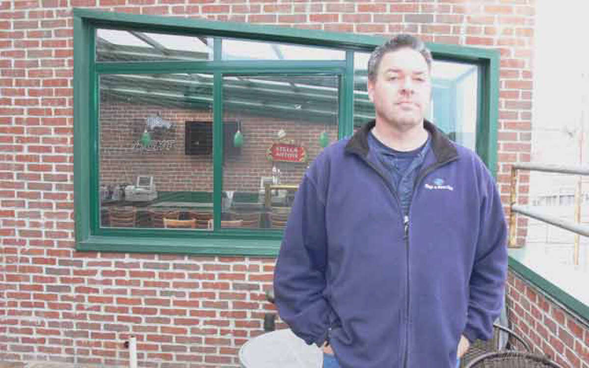Chris Jones, one of the new owners of the former Downtown Danny O's in Shelton, stands on the second-floor outdoor patio.