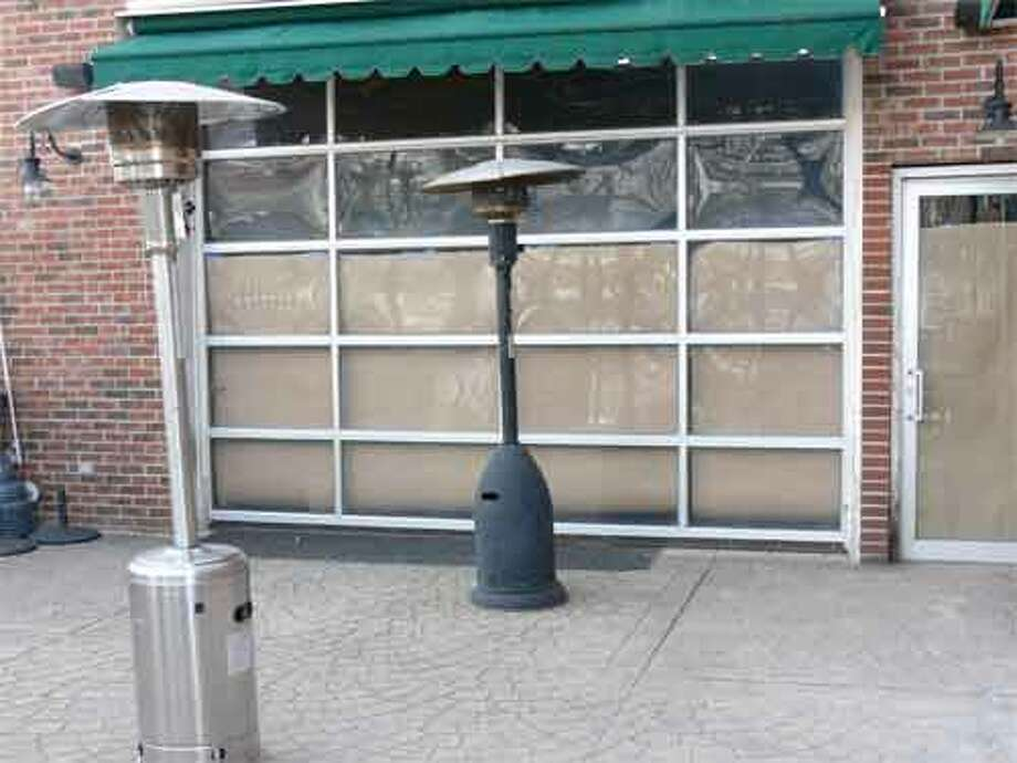 The empty patio at Downtown Danny O's, with brown paper on the windows to cover the inside of the establishment.