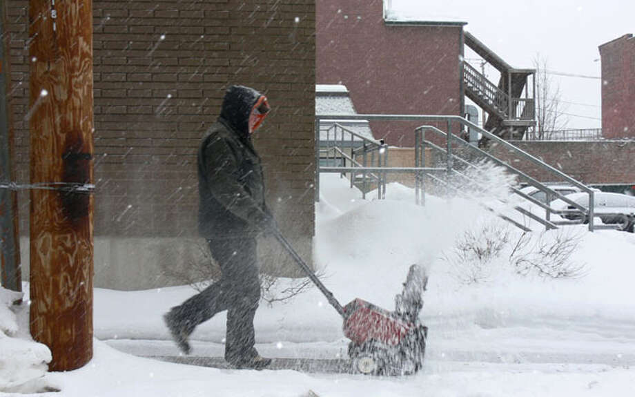 A man uses a snowblower to clear snow from the sidewalk near the Dunkin' Donuts at Howe Avenue and Center Street.