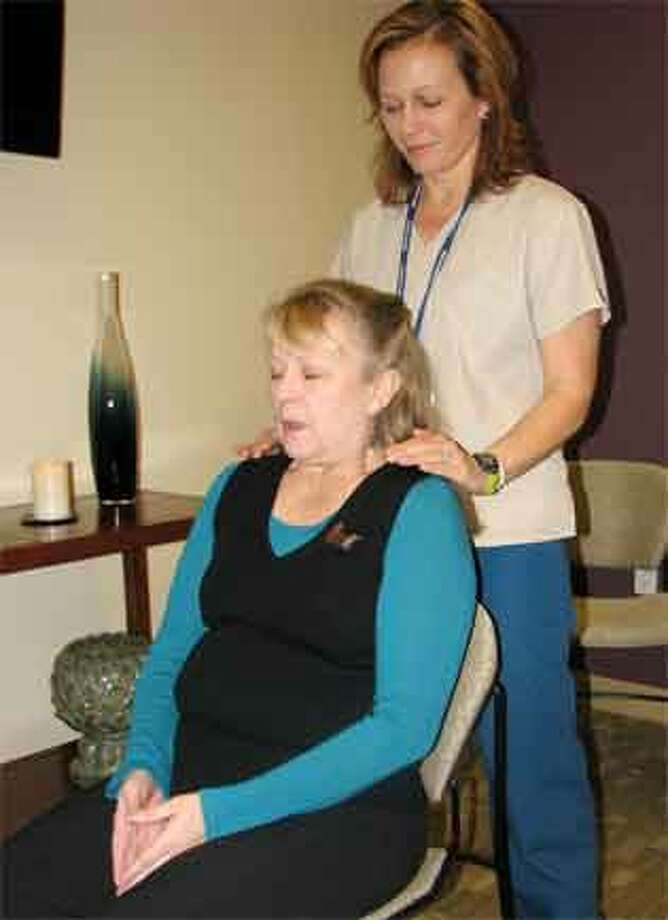 Griffin Hospital radiation therapist Laura Howell performs a Reiki treatment on Kim O'Neill, a massage therapist at Griffin.