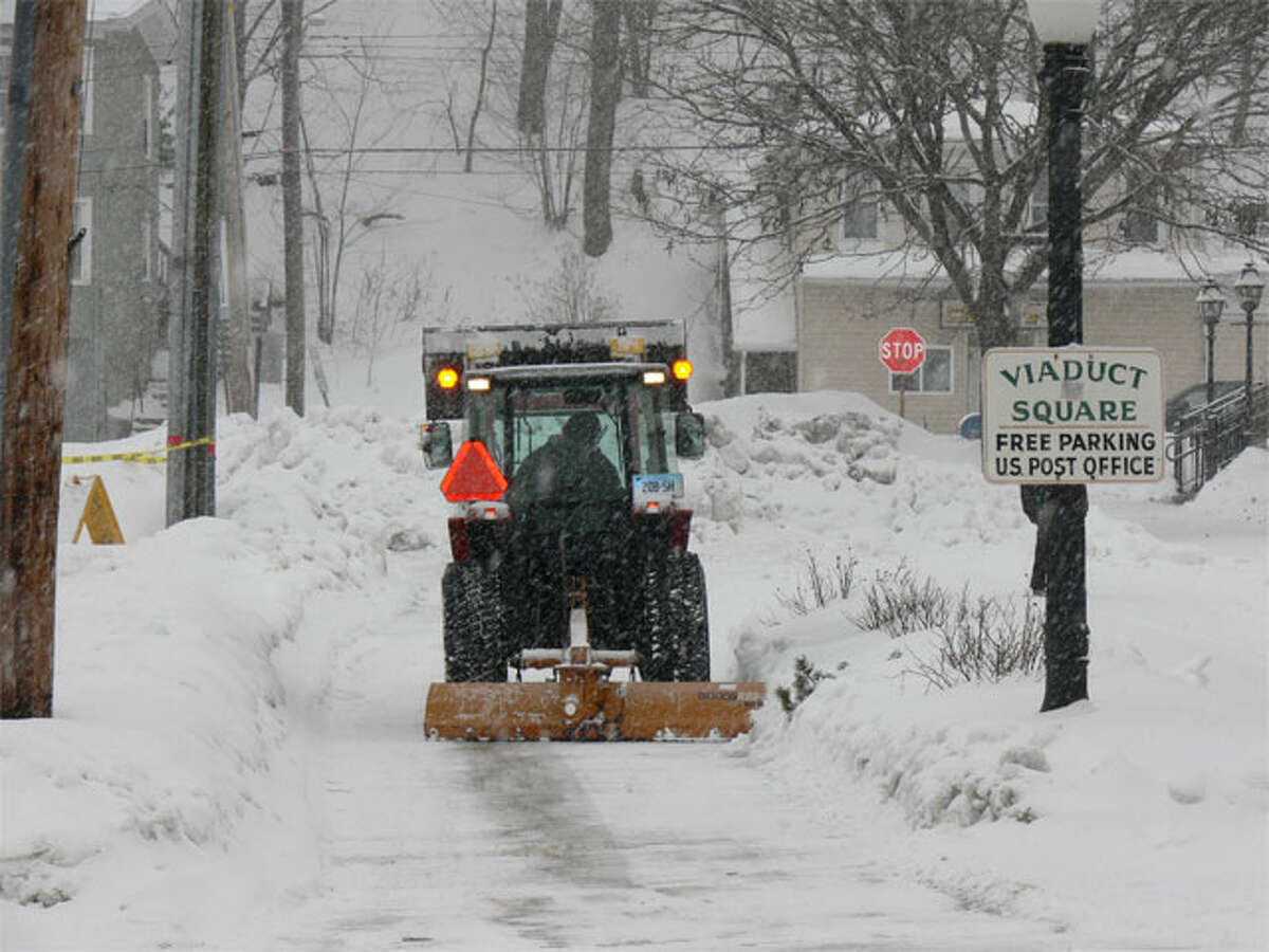 A city worker clears snow from Bridge Street, near the post office, at the height of the storm on Thursday morning.