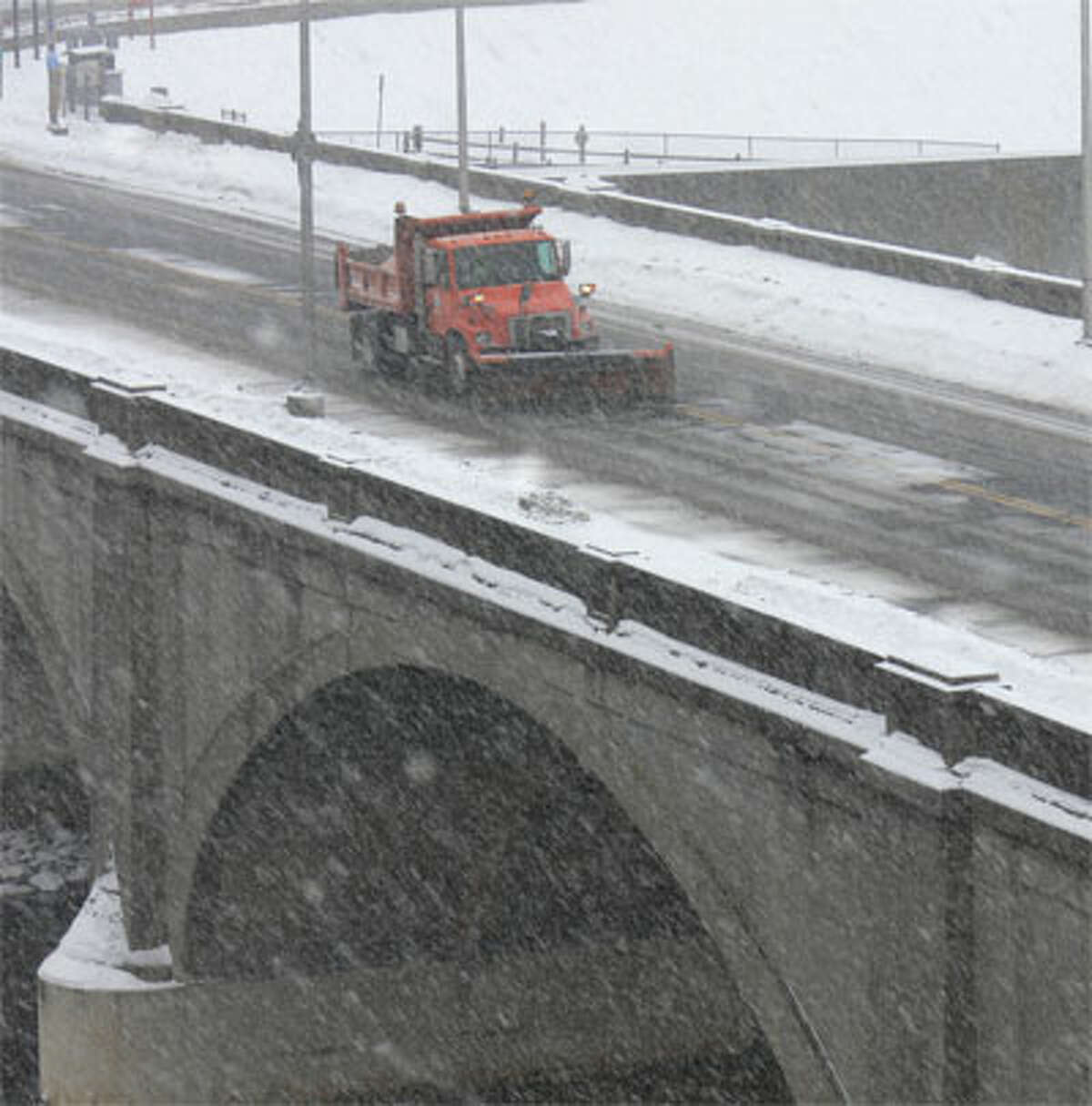 A plow clears snow on the Derby-Shelton Bridge over the Housatonic River.