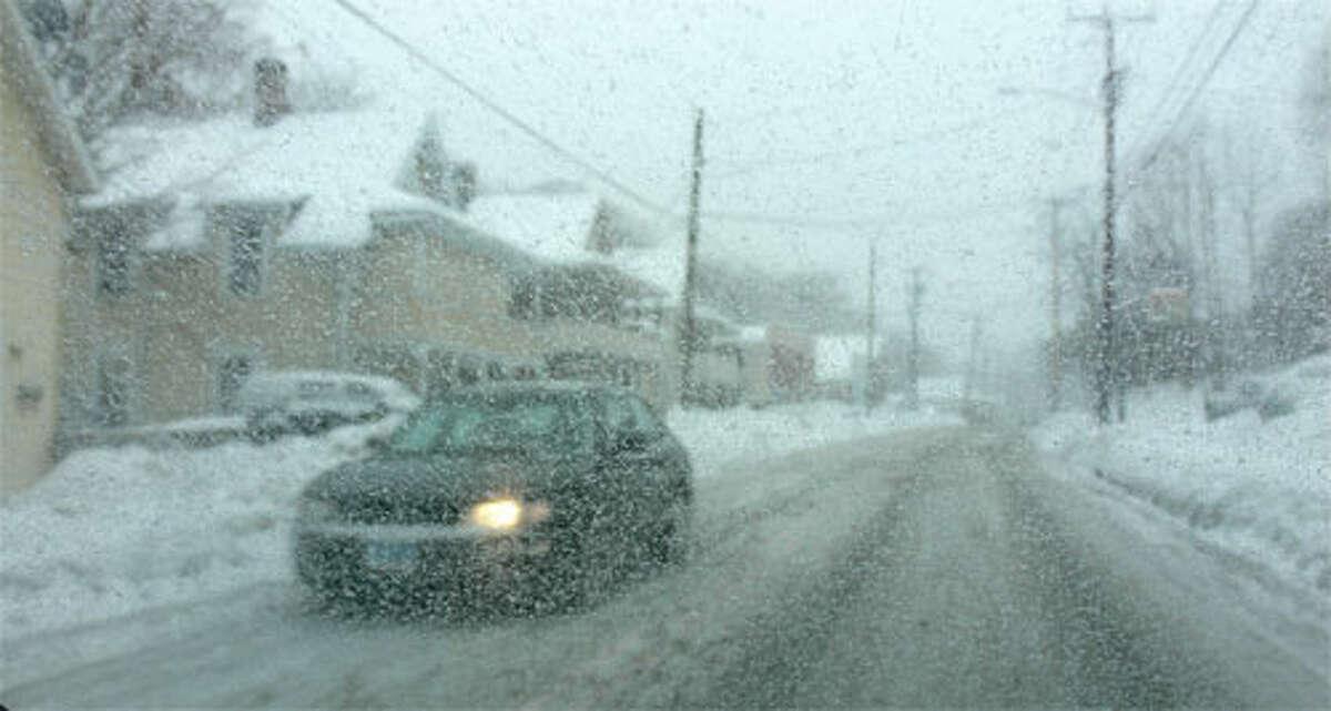 Snow falls on Bridgeport Avenue, near downtown Shelton, during a past storm.