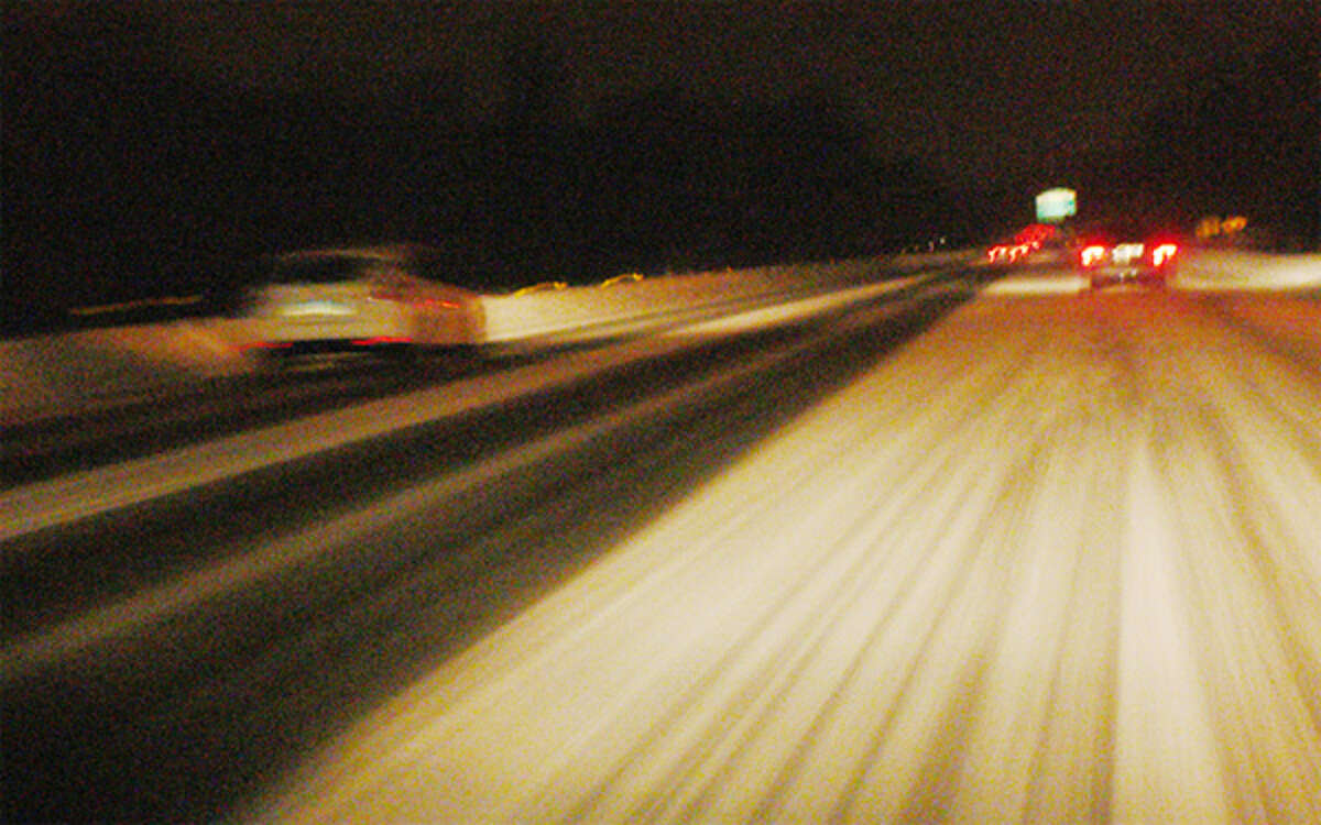 Vehicles travel on a snow-covered Route 8 through Shelton on Sunday night.