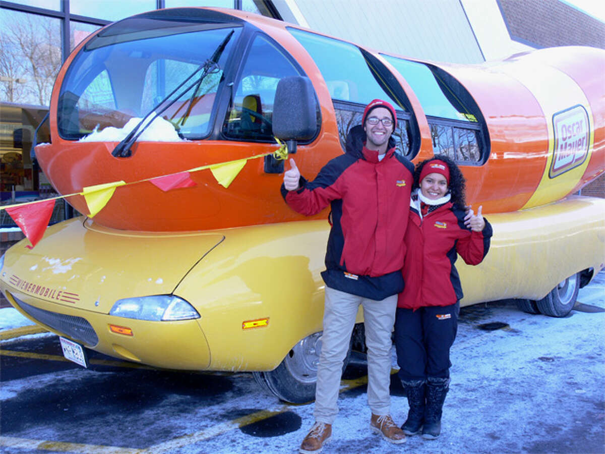 Michael Tierney of Minnesota and Amanda Vazquez of New York give the thumbs up while standing next to their Wienermobile at the Shelton Stop & Shop on Thursday.