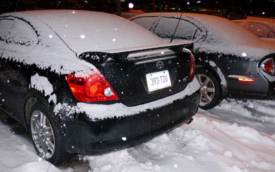 Snow begins to cover parked cars during an evening flurry in Shelton on Sunday, Feb. 16.