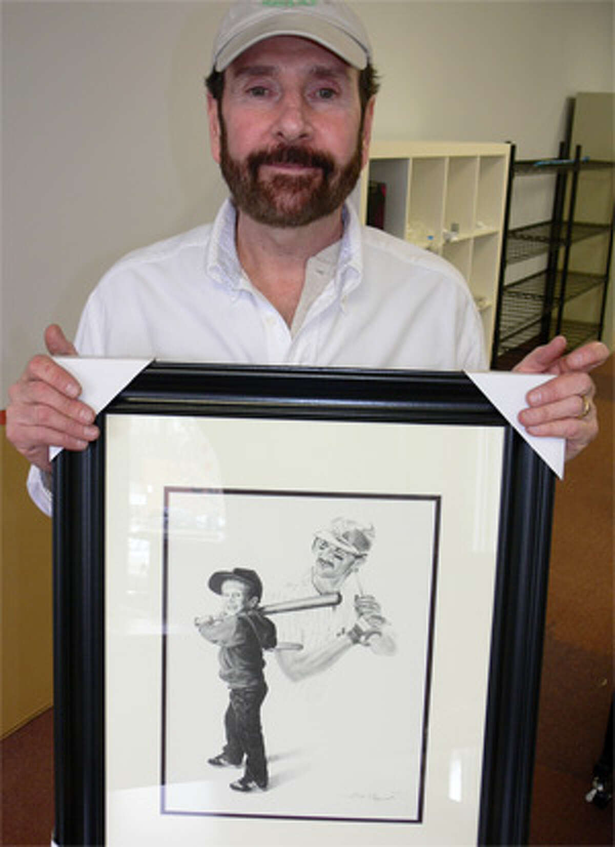 Bob Boroski holds a framed drawing he did many years ago of his son and Yankee player Don Mattingly.
