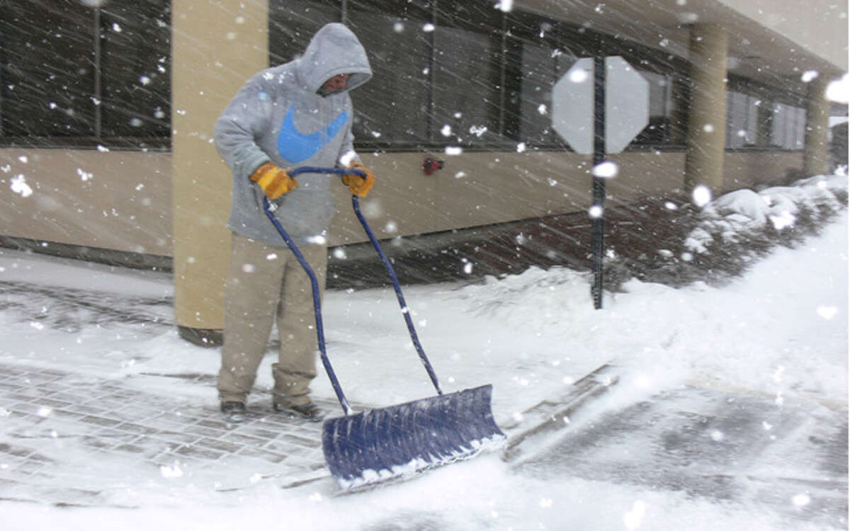 A worker shovels snow on Thursday morning from a walkway near the entrance of an office building in Shelton.