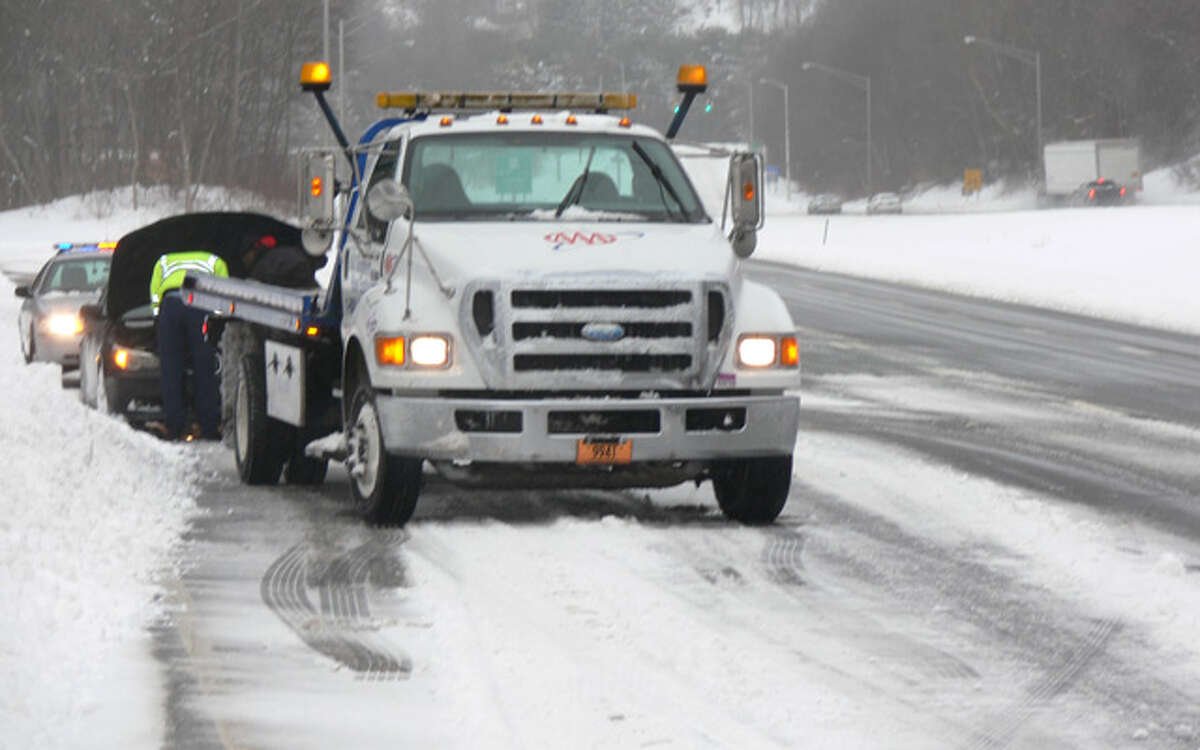 A tow truck driver and state trooper assist a motorist on the side of Route 8 southbound, near Exit 13 in Shelton, at about 2:30 p.m. Thursday.