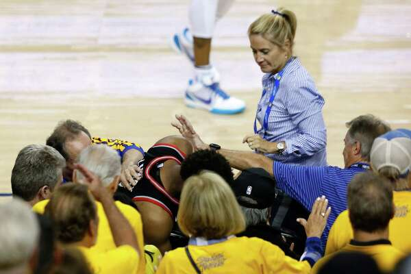 OAKLAND, CALIFORNIA - JUNE 05: Kyle Lowry #7 of the Toronto Raptors is pushed by a fan after falling into the seats after a play against the Golden State Warriors in the second half during Game Three of the 2019 NBA Finals at ORACLE Arena on June 05, 2019 in Oakland, California. NOTE TO USER: User expressly acknowledges and agrees that, by downloading and or using this photograph, User is consenting to the terms and conditions of the Getty Images License Agreement.