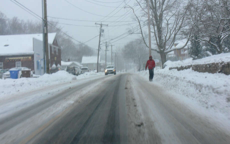 A man walks down Bridgeport Avenue in Shelton at the height of the storm in the late morning.