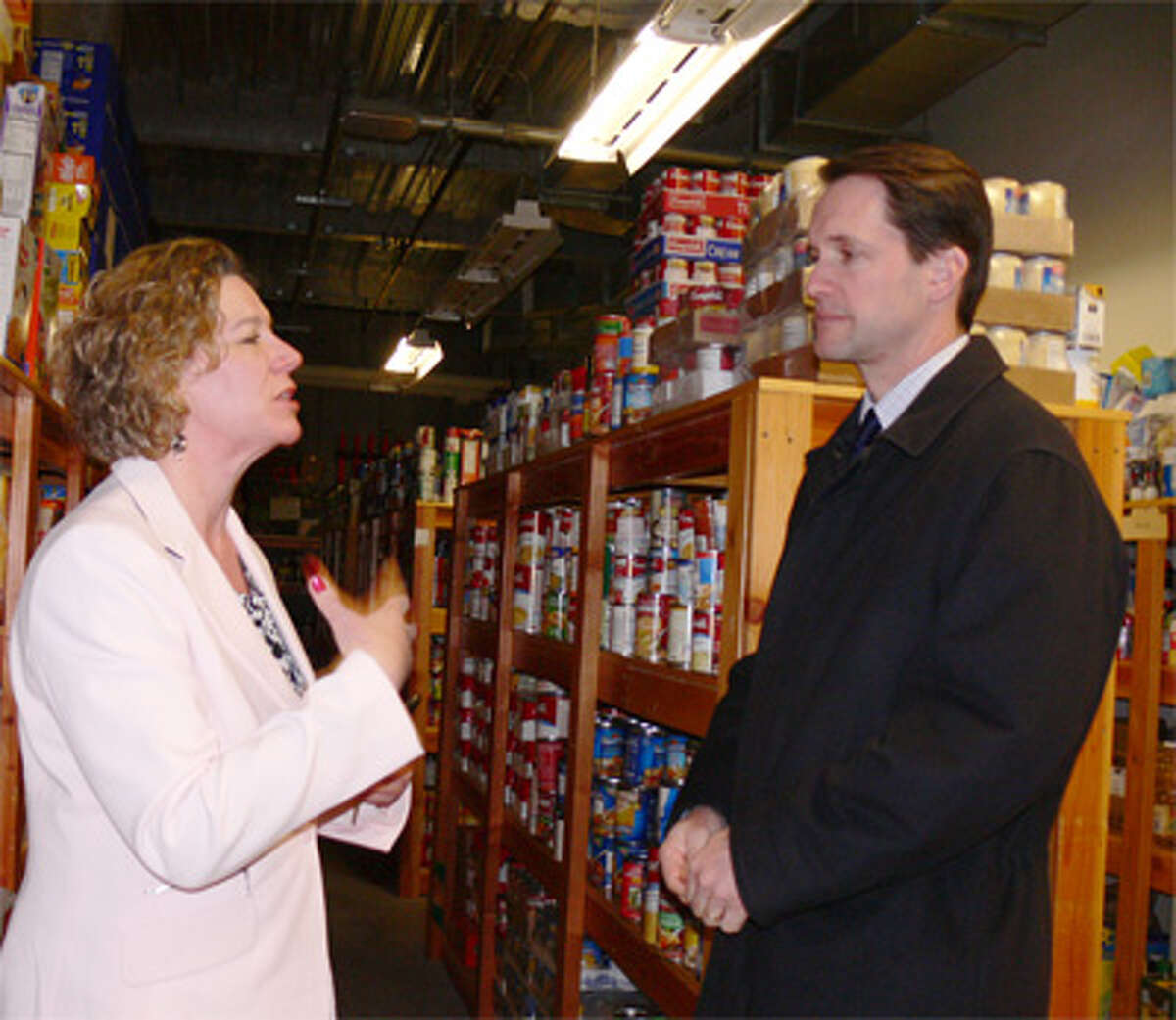 Susan J. Agamy, Spooner House executive director, describes the facility's food bank services to U.S. Rep. Jim Himes, who represents most of Shelton.