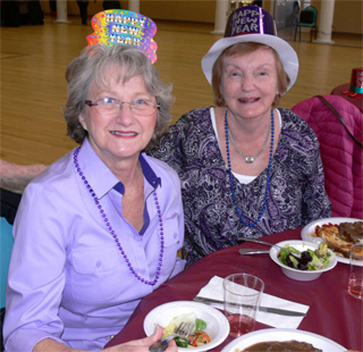 Mary Ann LeBlanc, left, and Edna Kerkes, both of Shelton, take a break from their meal while wearing their party hats at the Shelton Senior Center's New Year's gathering.