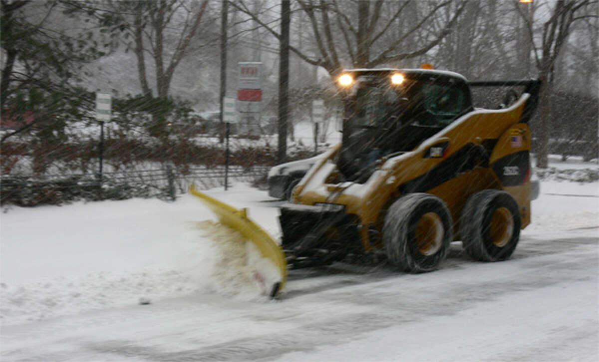 A private contractor clears a large commercial parking lot in Shelton during today's snowstorm.