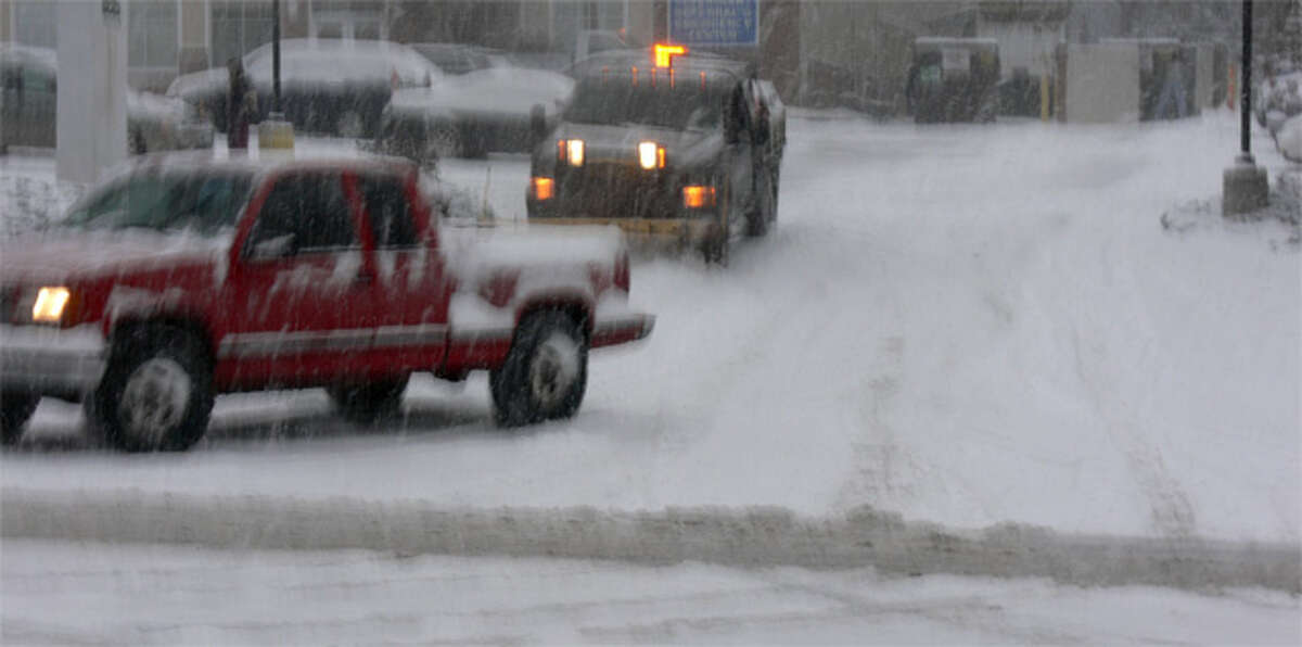 Vehicles, including a private plow, on the move late Thursday afternoon in Shelton as the snow began to accumulate.