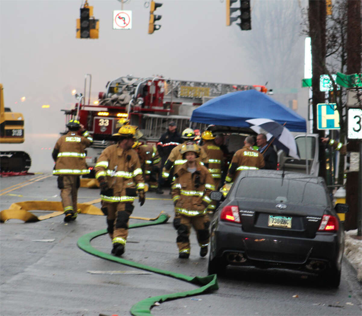 Firefighters move around the scene on Howe Avenue, with Mayor Mark Lauretti visible standing behind the car, holding an umbrella and talking to a fire official.