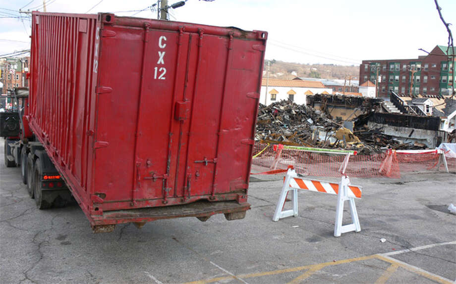 A container with fire debris is lifted onto the back of a truck on Friday afternoon to be transported off-site.