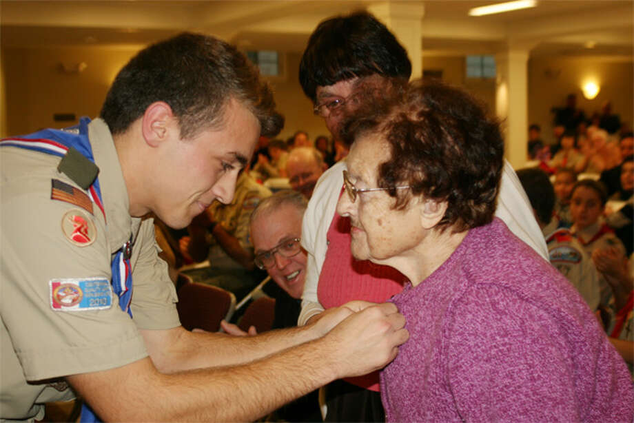Eagle Scout Chris Haack' grandmother Jo Petrie looks on as he presents a mentor pin to his great-grandmother, Ida Minolaio, who taught him at a young age the gardening skills he used for his Eagle project.