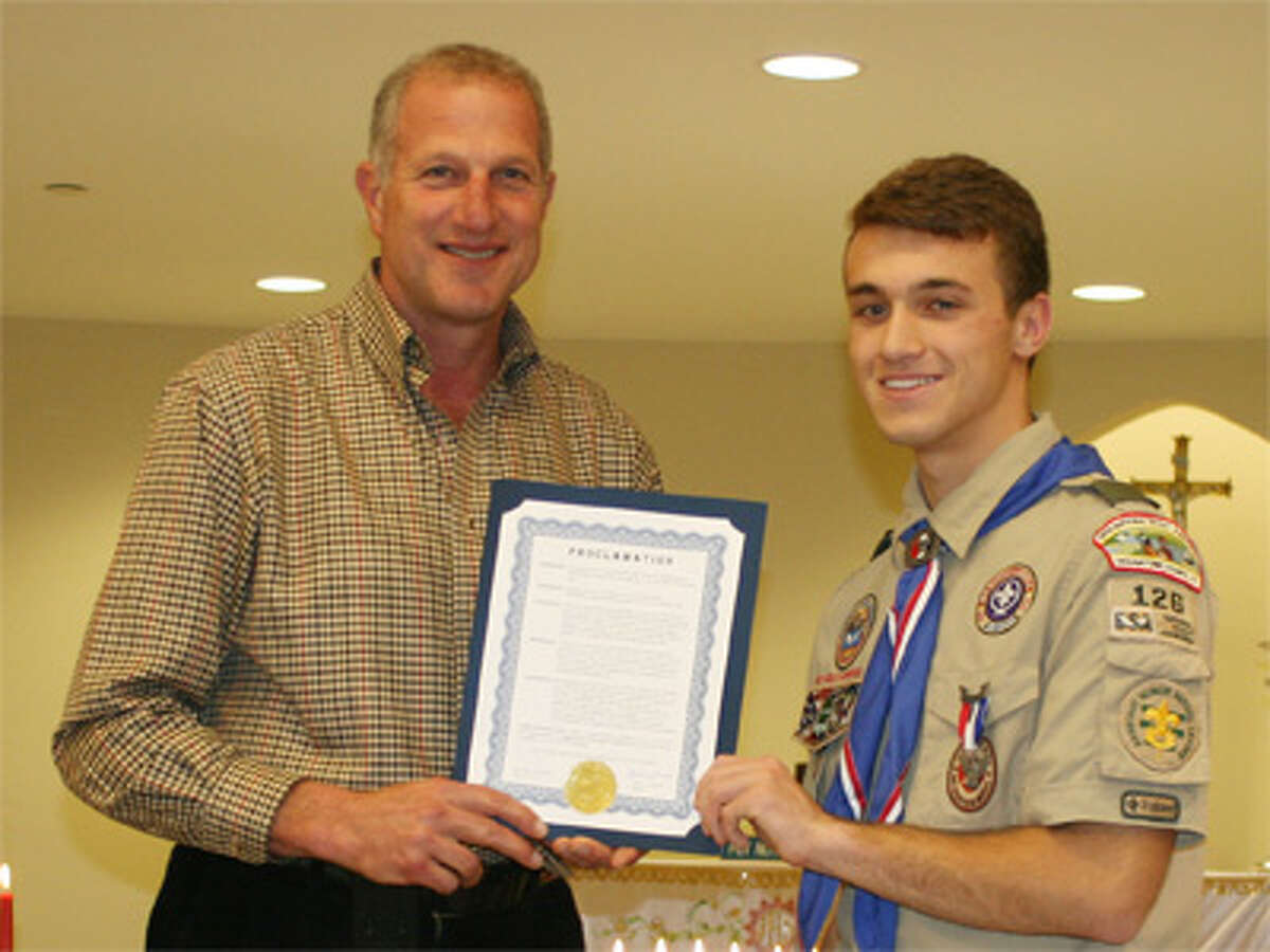 Mayor Mark Lauretti presents Shelton Eagle Scout Chris Haack with a proclamation to mark his accomplishment.