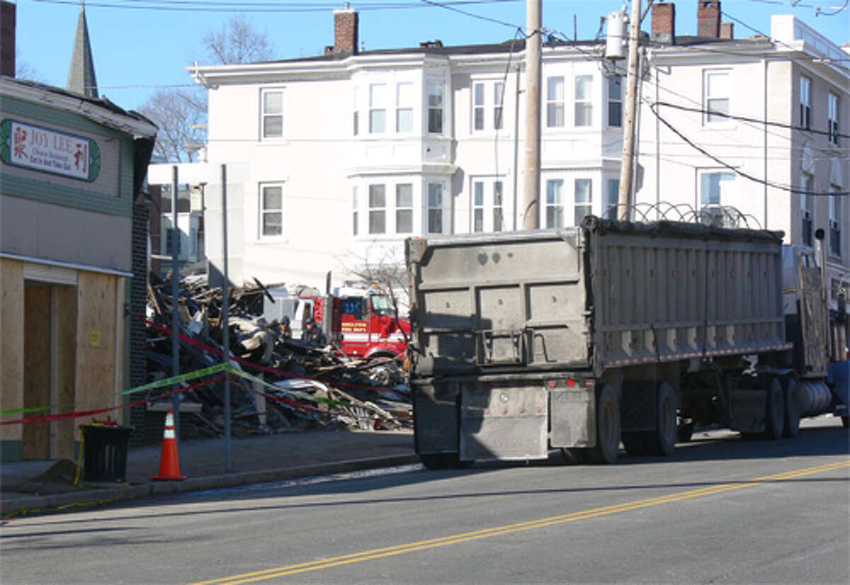 A truck on Howe Avenue waits to be loaded with building debris so it can be trucked off-site on Thursday early afternoon.