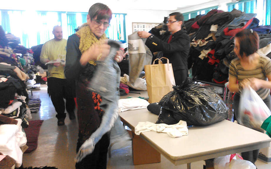 U.S. Rep. Rosa DeLauro joins others to help sort clothing items donated for fire victims on Tuesday morning at the Echo Hose firehouse. (Photo by Robin Walluck)
