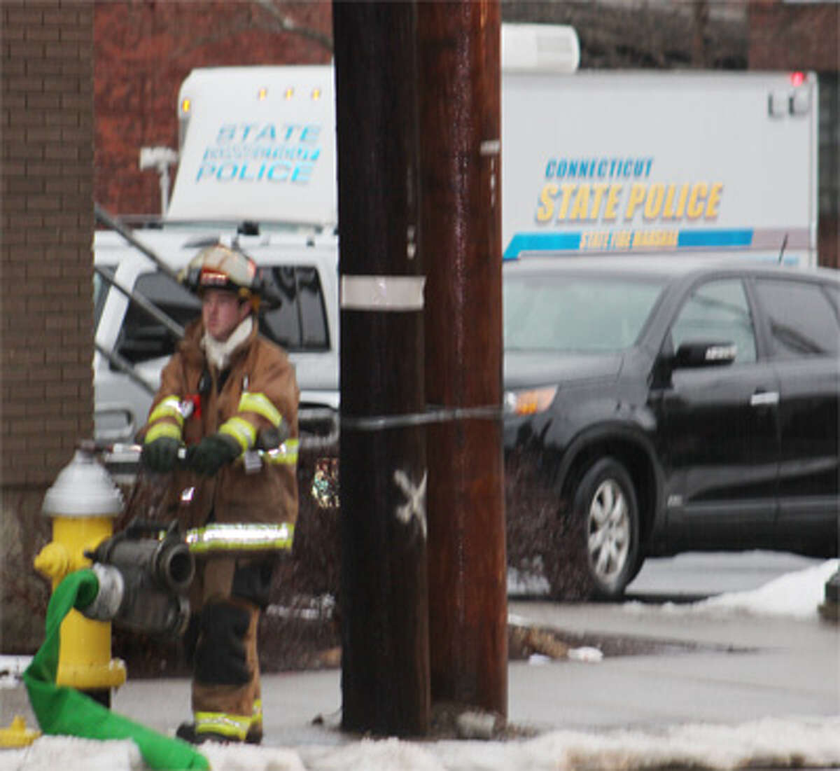 A firefighter taps into a fire hydrant on Center Street, just off Howe Avenue toward the Housatonic River. Note the State Police Investigation van behind him, in the Dunkin' Donuts rear parking lot.