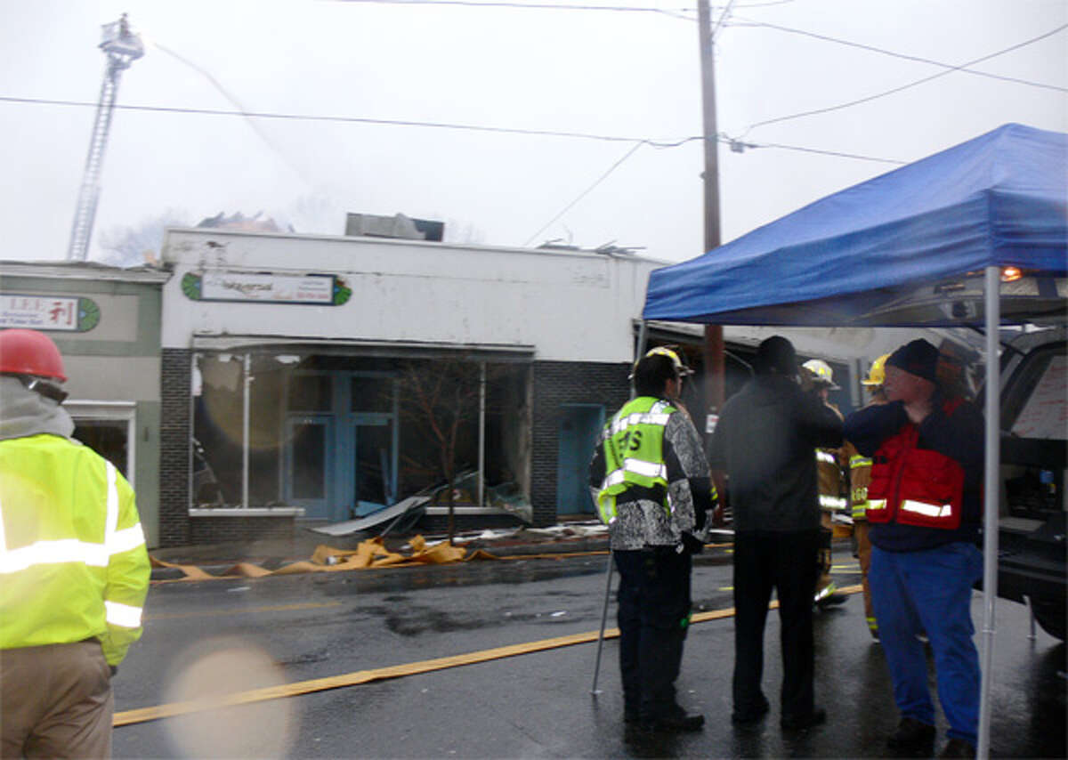 Fire personnel discuss the situation under a tent at about 8:30 a.m. Monday, when the downtown Shelton fire had essentially been put out. Note the firefighter with a hose on the crane in the background.