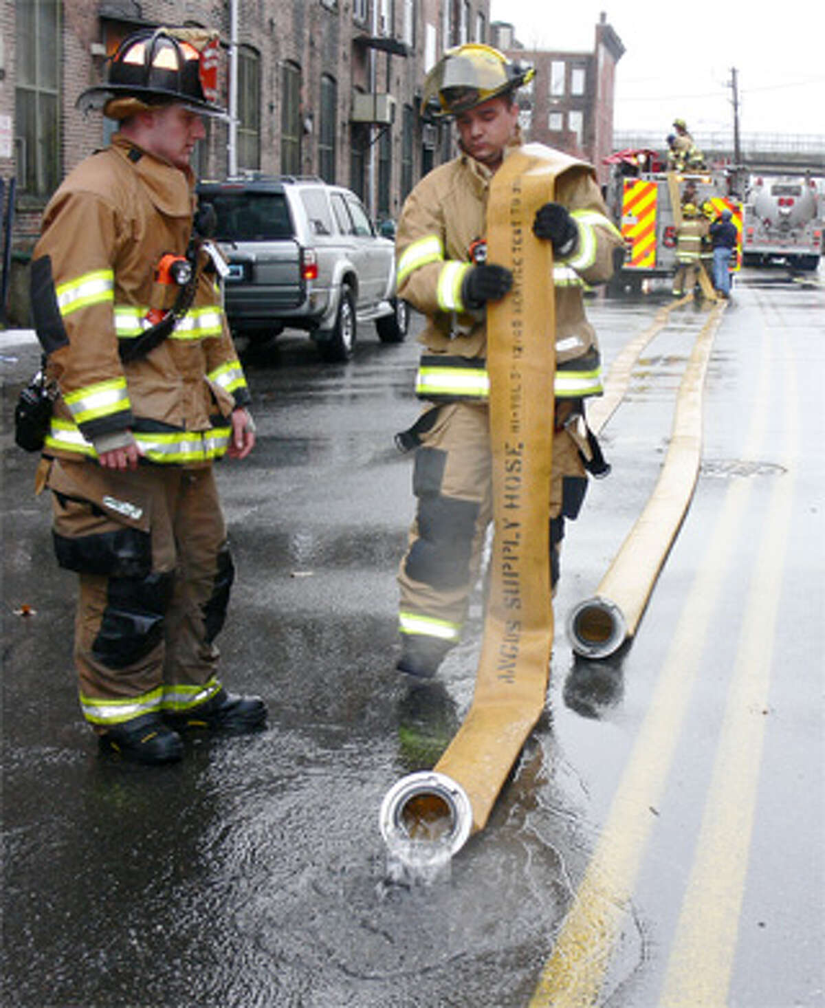 Two Shelton volunteer firefighters empty water from, and roll up, a fire hose used while battling the downtown Shelton fire on Monday.