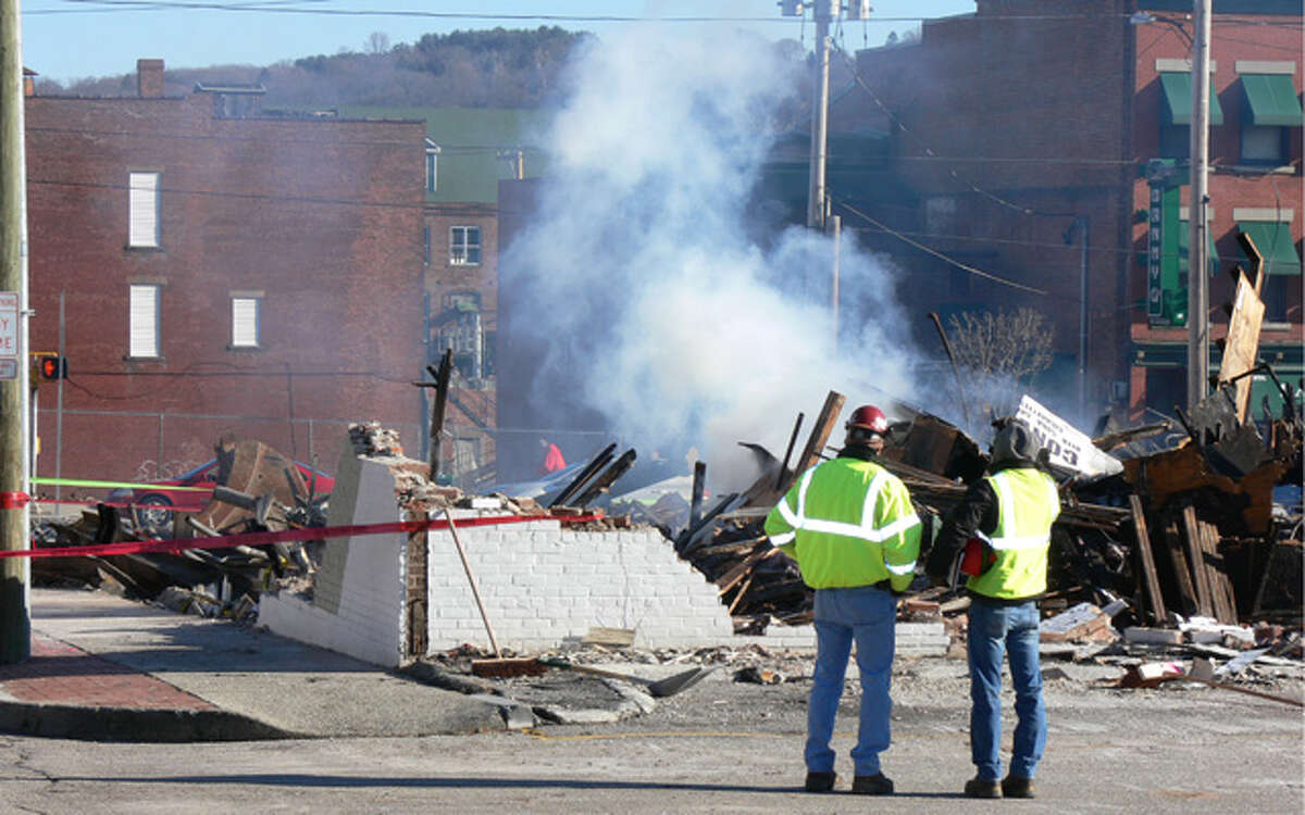 Workers at the fire scene observe smoke from a hotspot at the downtown Shelton fire scene on Tuesday morning.
