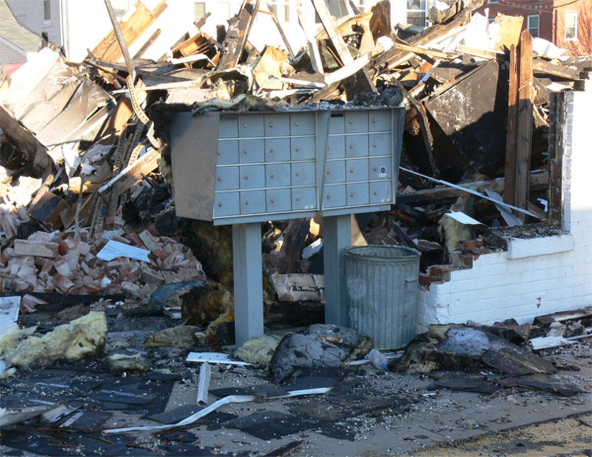 The surviving mailbox from the apartment complex is surrounded by debris from the Shelton fire.