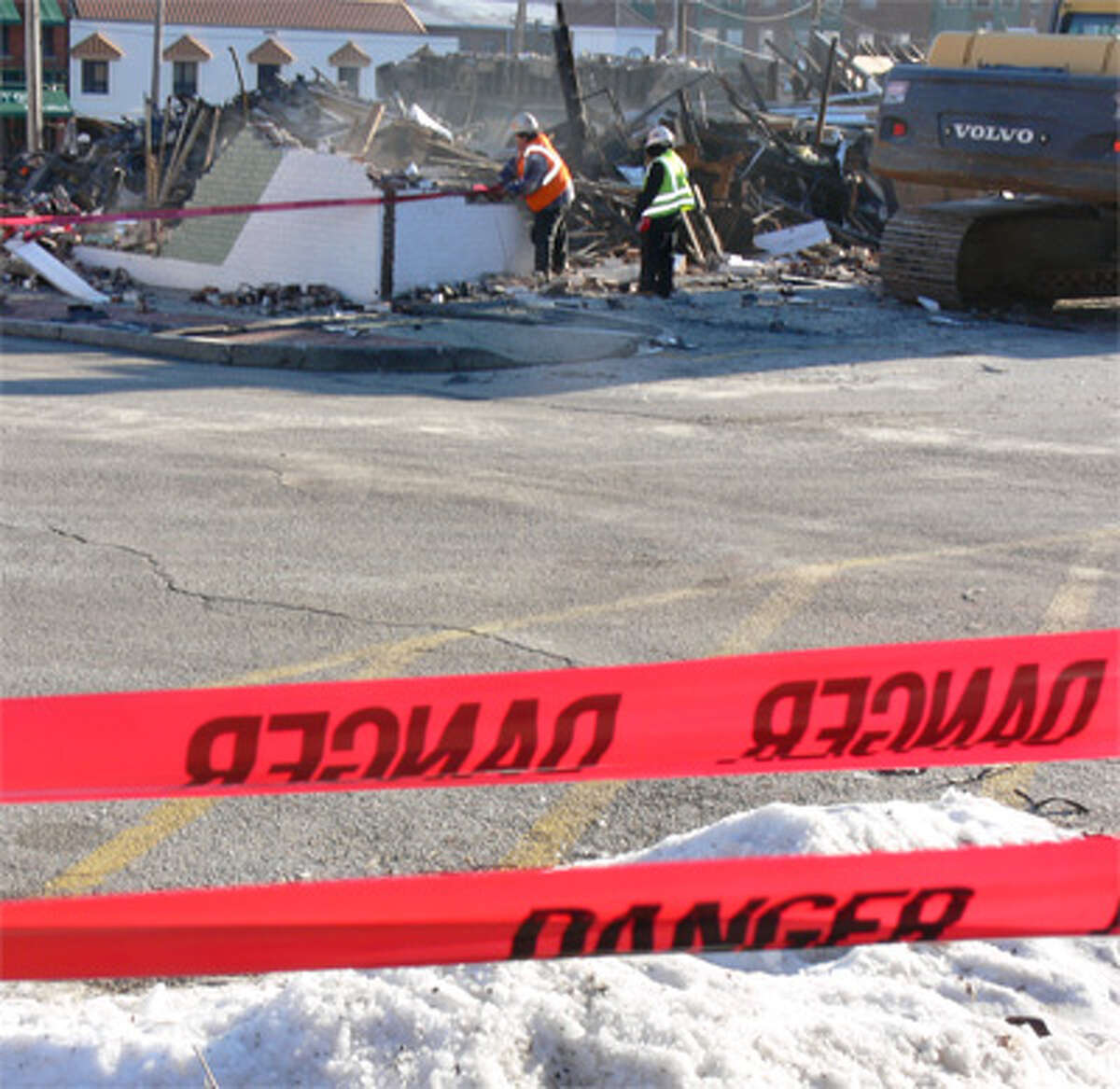 Police tape near the Shelton post office keeps onlookers away from where workers are continuing to take apart remnants of the collapsed building.