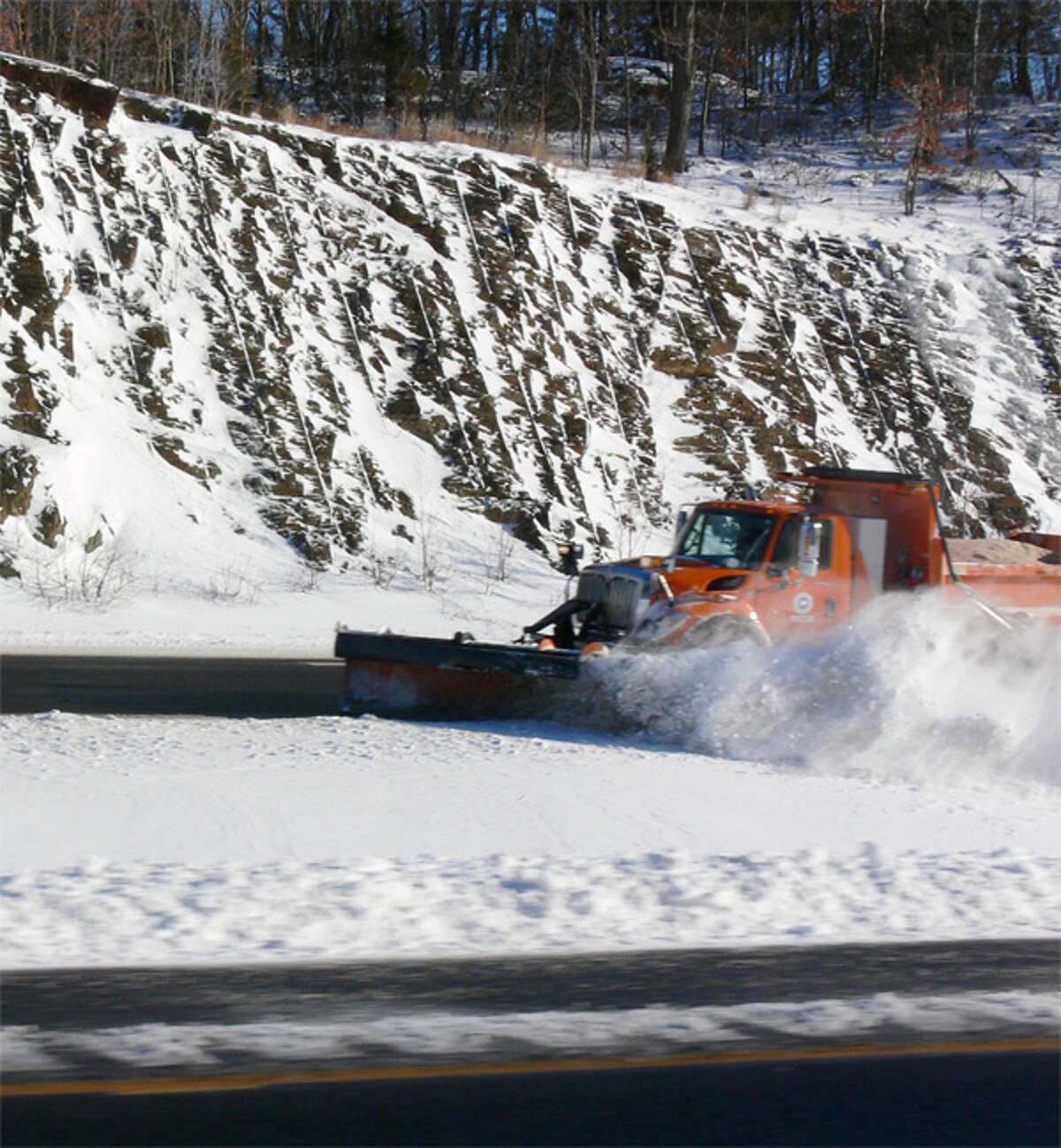 A state DOT plow clears snow from Route 8 northbound in Shelton, just north of the Old Stratford Road exit.