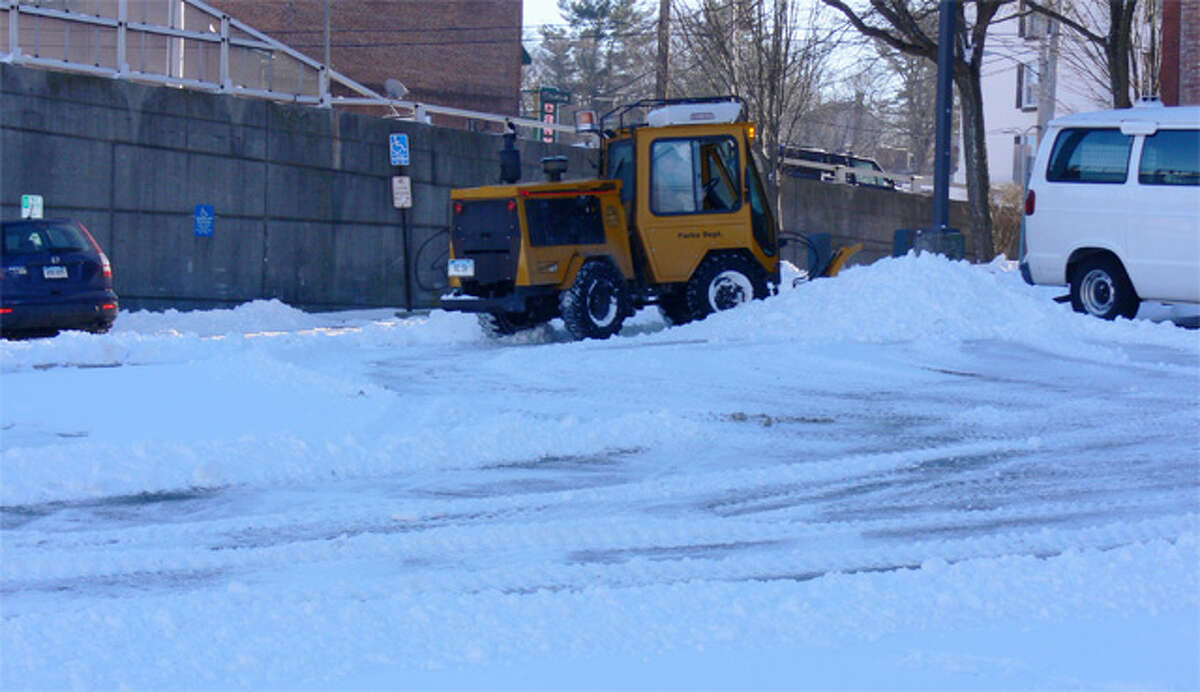 A small snow-clearing vehicle is used to plow a downtown Shelton parking lot after the snowstorm.