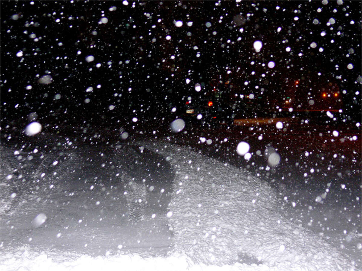 Private snowplows form piles of snow near Bridgeport Avenue on Thursday night as the snow begins to accumulate.
