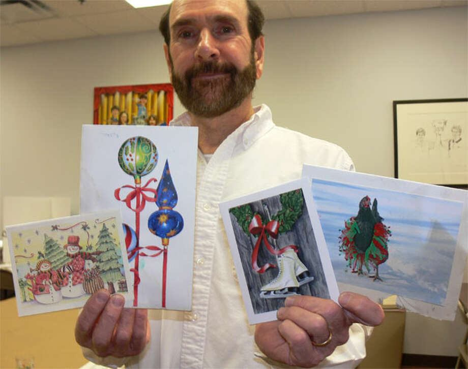 Bob Boroski holds holiday cards made by students at his art school through the years that survived the massive downtown fire last January. Some of the cards are charred from the blaze and most still smell of smoke.