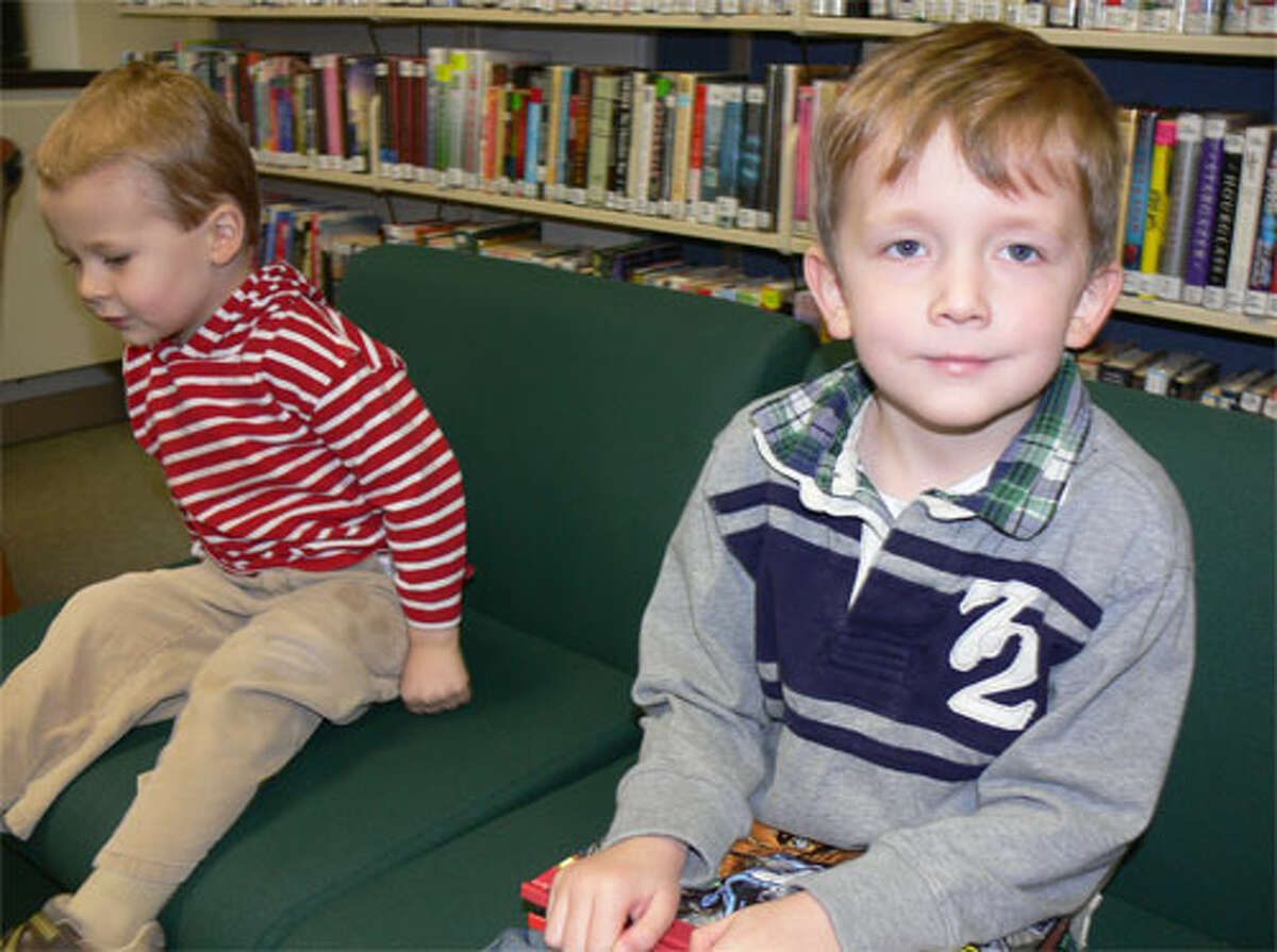Joey Dumas, 5, of Shelton, with 3-year-old Nicholas Rose in the background, waits for story time during Meet Santa Day.