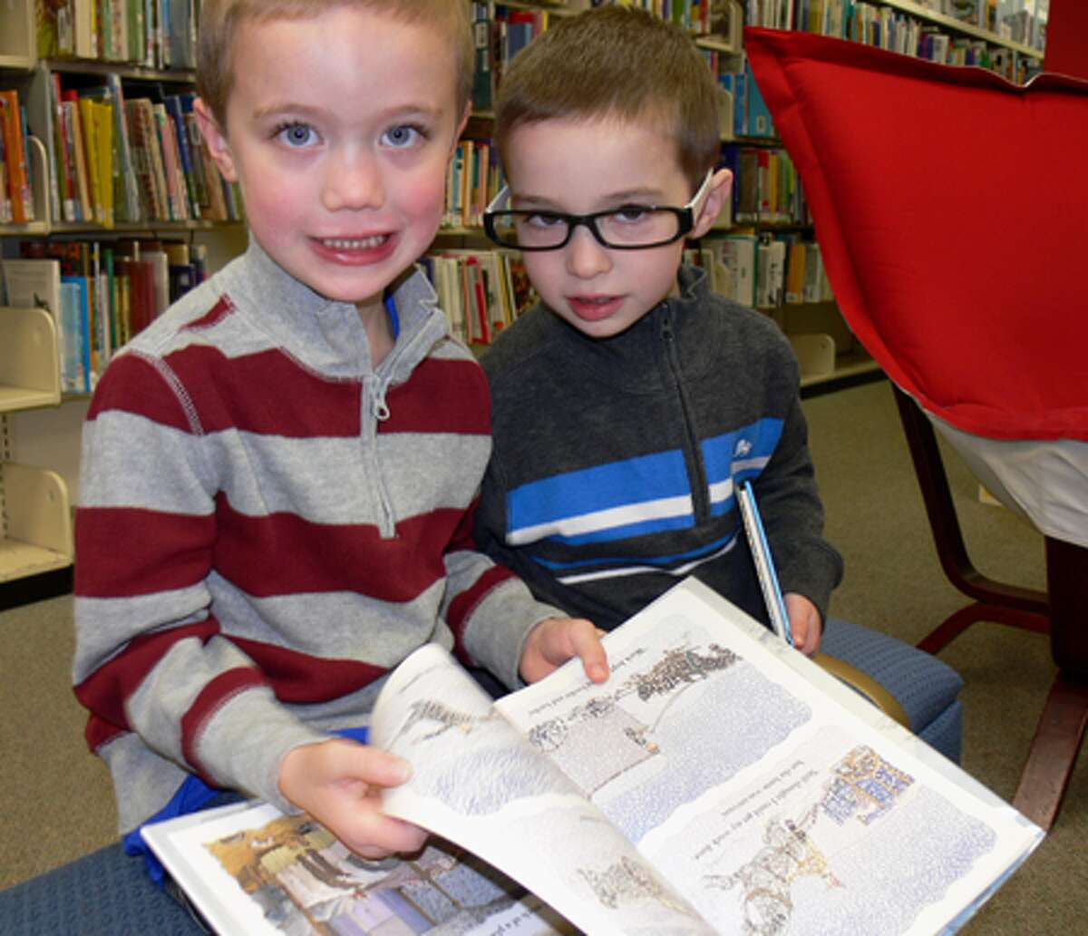 Nolan Royce, 5, and his brother Landon, 4, take a break from reading a book while waiting to meet with Santa at the library.