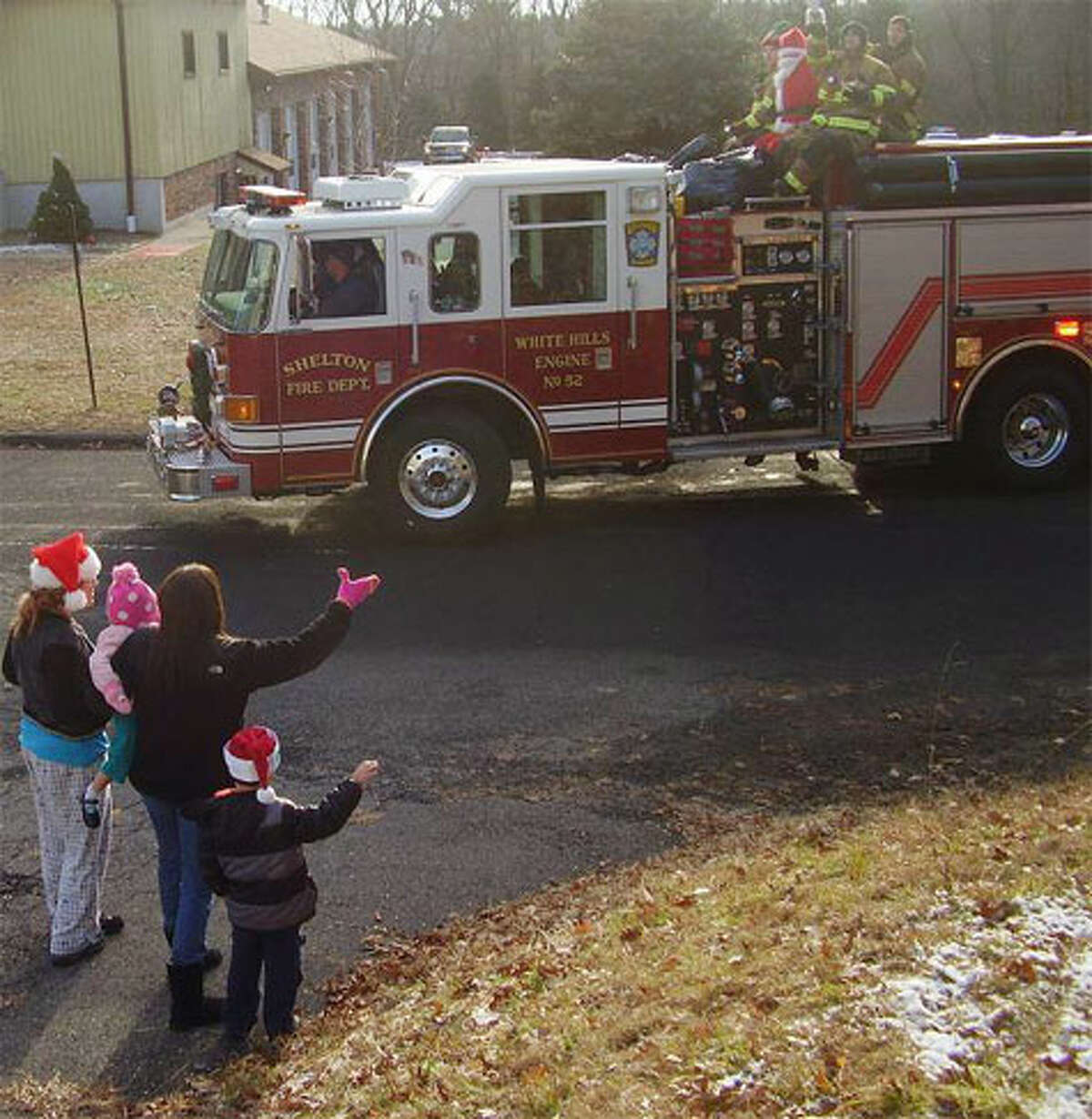 Santa and his elves on a firetruck as they begin their journey through the White Hills of Shelton.