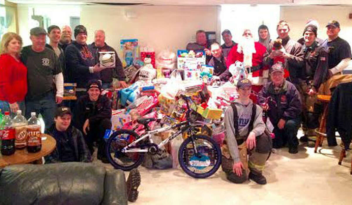 Santa Claus and his team with the all toys collected during the ride through the neighborhood.