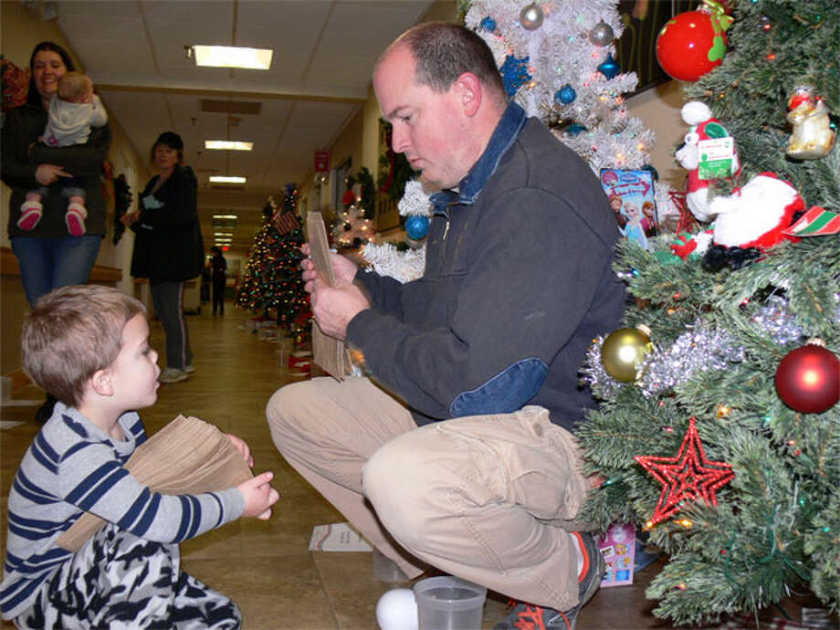 Max Aulet, treasurer of Echo Hose Fire, puts numbers on raffle bags at the Festival of Trees while assisted by his son Alex, 3.