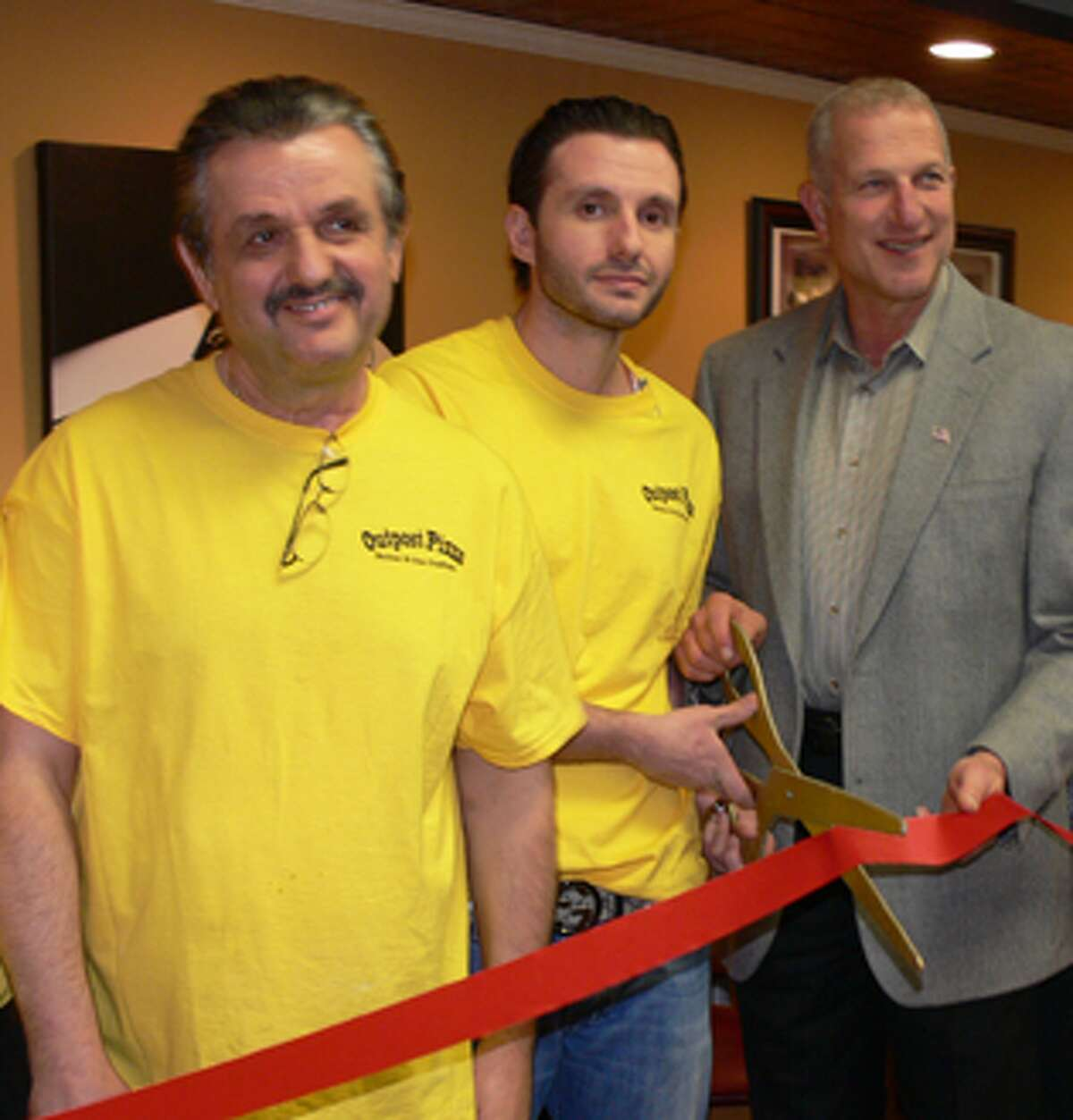 From left, Tom Dedovic, Joe Dedovic and Mayor Mark Lauretti at the ribbon-cutting ceremony for the new pizzeria.