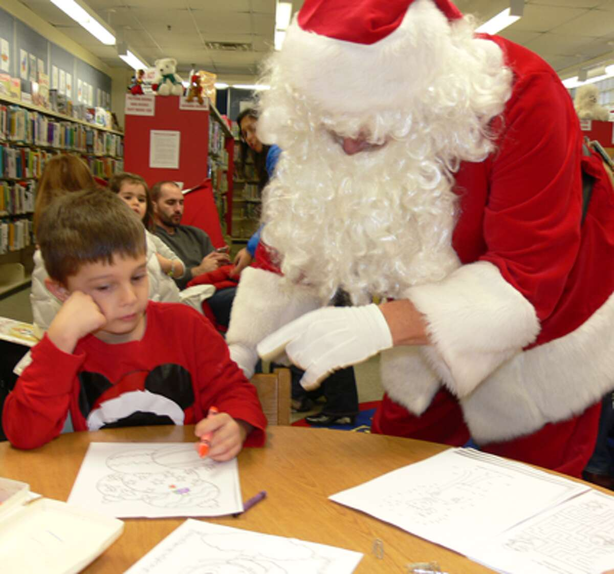 Santa compliments a drawing by a youngster during the event at the Huntington Branch.