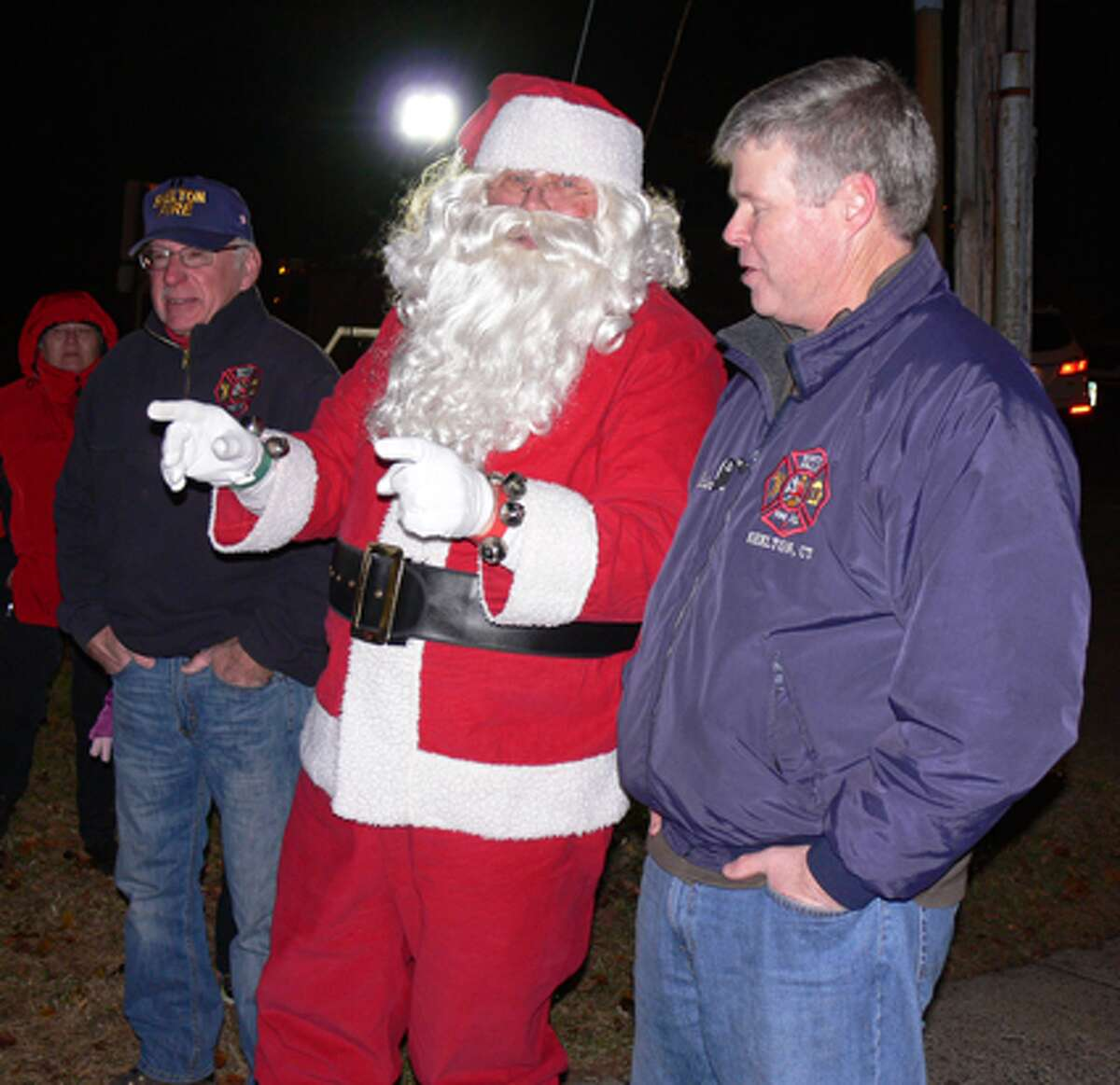 Santa chats with the fire company's Brian McCue after arriving by firetruck to meet with children from the neighborhood.